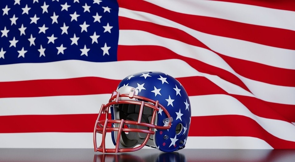 A football player's helmet in front of an American flag