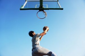 A basketball player dunking a ball into the basket