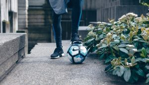A man with his foot on top of a football