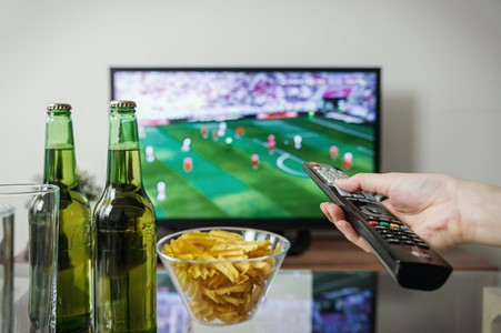 Watching a game on TV with snacks and drinks