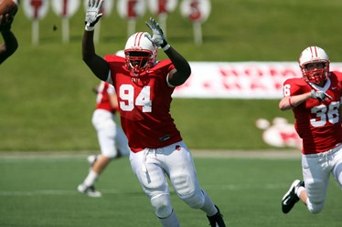 Football player in red jersey raising his hands in the air for a pass
